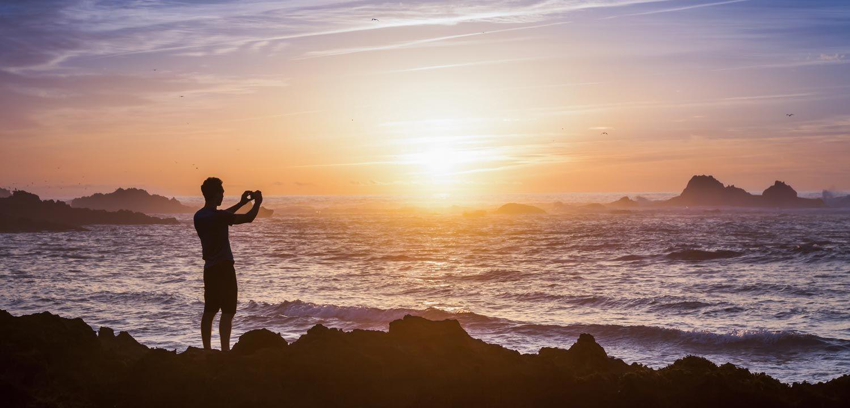 Erlebnisreisen in Marokko, ein Mann steht am Ufer der marokkanischen Atlantikküste und schießt ein Foto