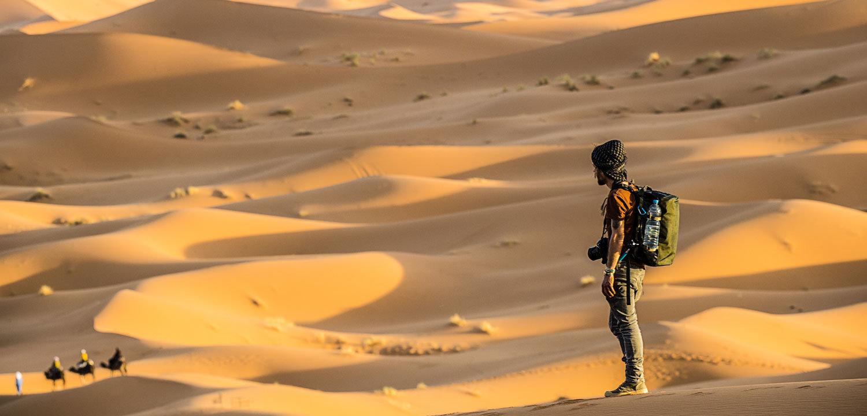 Marokko Adventures Erlebnisreisen Marokko, ein Mann auf einer Düne in der Wüste von Marokko